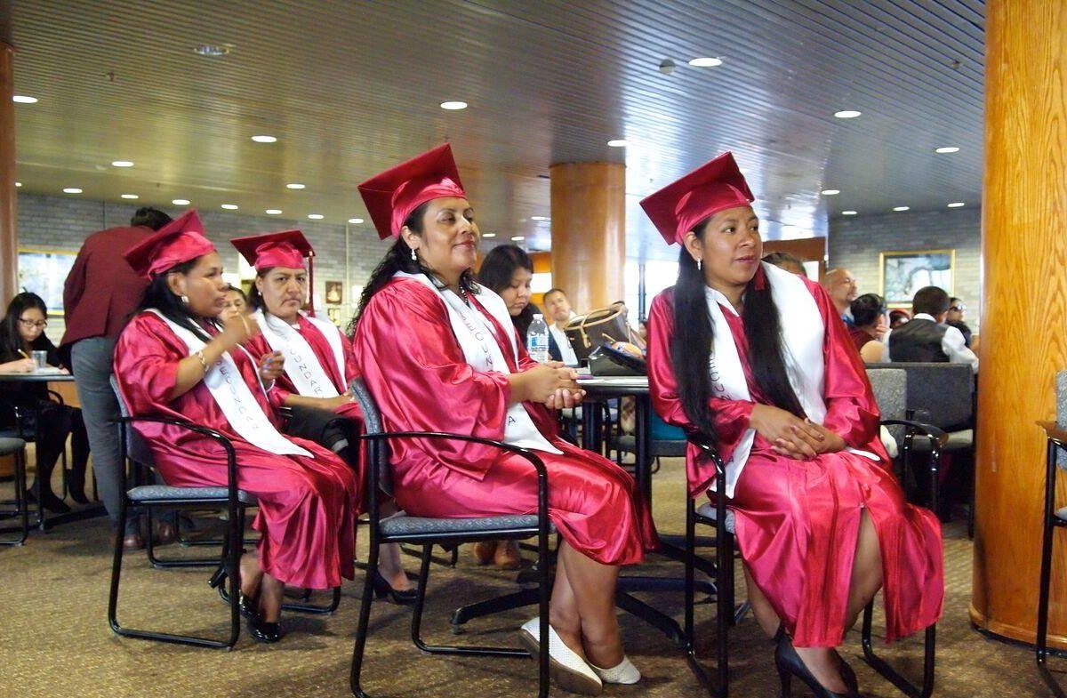 Photograph of several latina women in graduation caps and gowns sitting in rows.