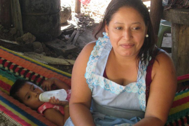 Salvadoran woman wearing a light blue apron sits on the edge of a hammock. Behind her in the hammock a toddler lays drinking a bottle.