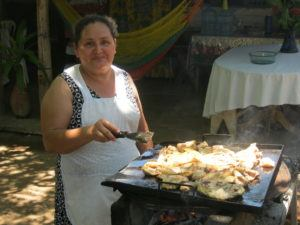 A woman wearing an apron cooking tortillas on a flat grill outside.