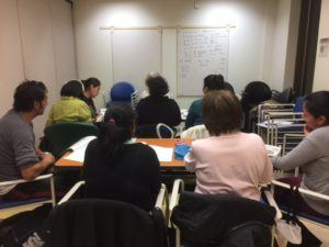 Photo of a classroom full of students taken from the back facing a white board with writing on it.