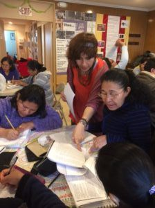 Photo of several women sitting around a table writing in educational workbooks. An instructor is standing pointing out a question in one of the workbooks.