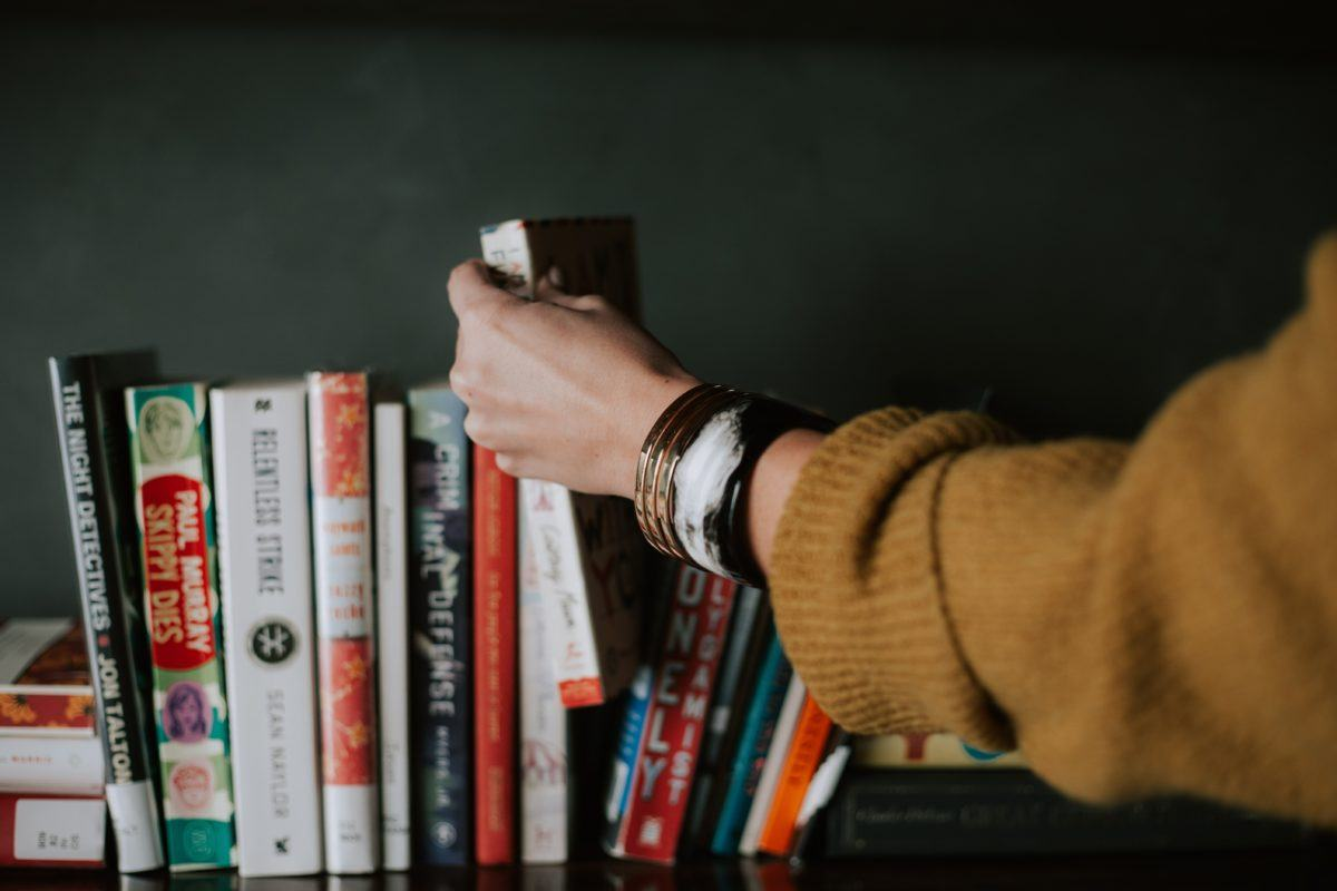 Photograph of a woman's arm and hand picking up a book from a shelf full of different colored books.