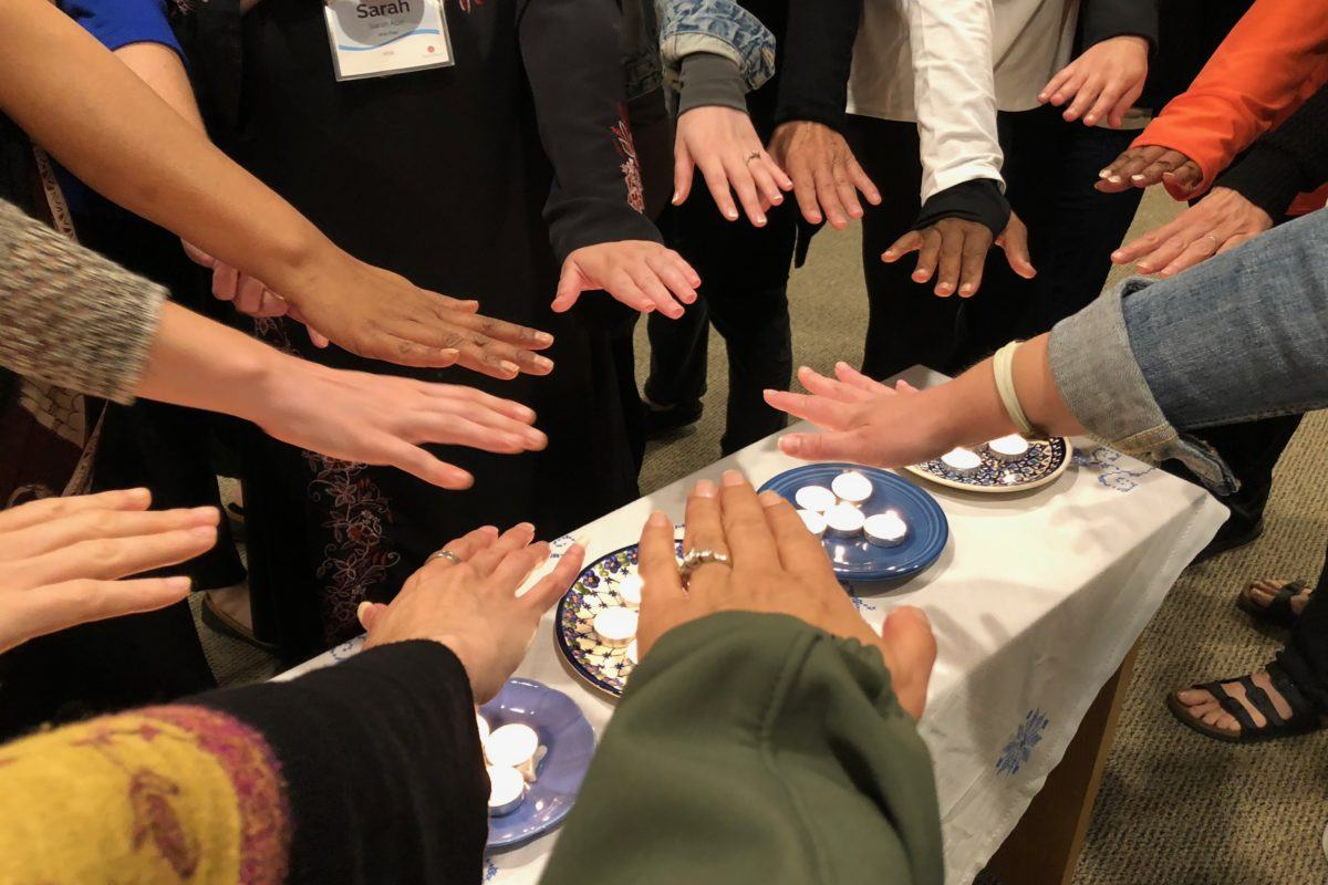 Photograph of 15 diverse women's hands stretched out toward each other in a circle.