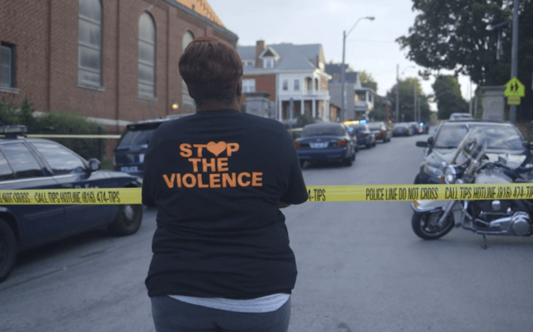 Photograph of a woman from the back, looking across police tape. Her shirt reads Stop the Violence.