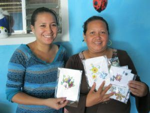Photograph of two women standing in front of a bright blue wall holding up handmade cards.