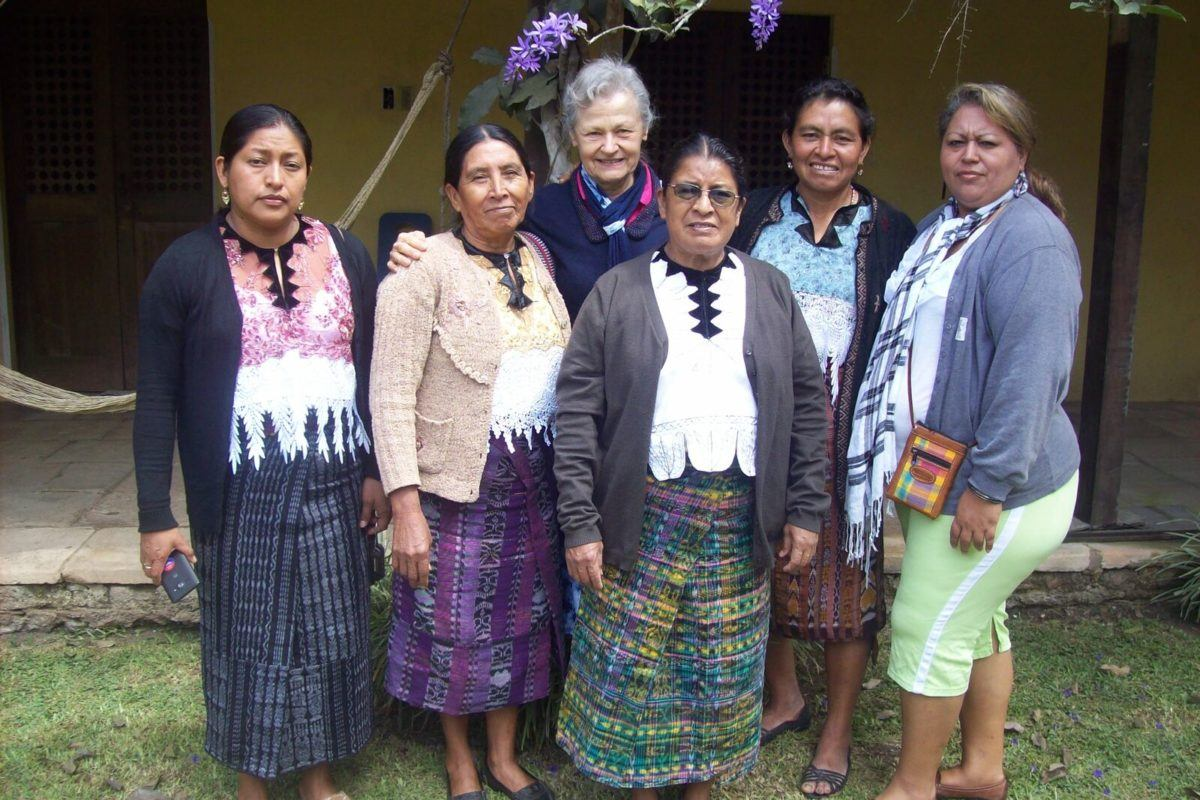 Photograph of several guatemalan woman in traditional dress, one woman from El Salvador, and one woman from the United States.