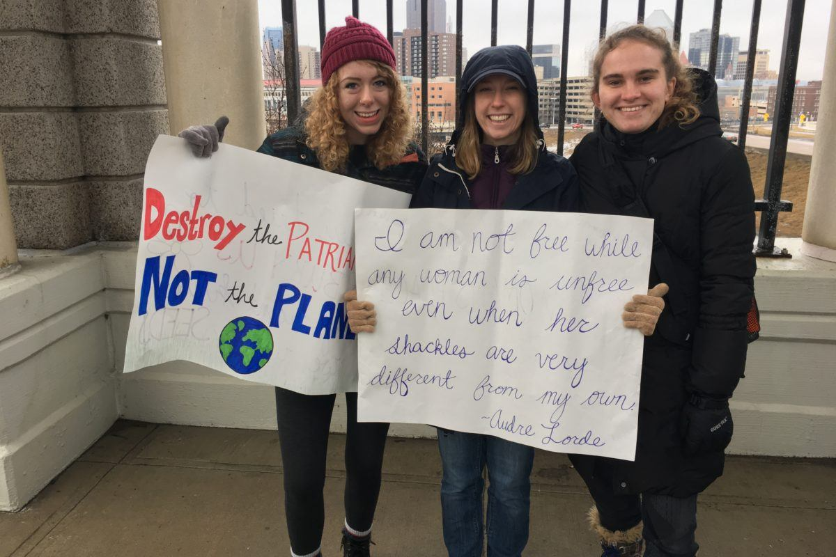 "Photograph of three young women holding signs that read ""destroy the patriarchy, not the planet"" and ""I am not free while any woman is unfree, even if her shackles are very different than my own.. - Audre Lorde"""