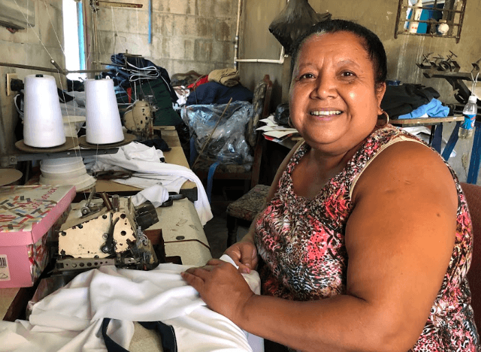 Photo of woman sitting at sewing machine showing her seamstress shop in El Salvador.