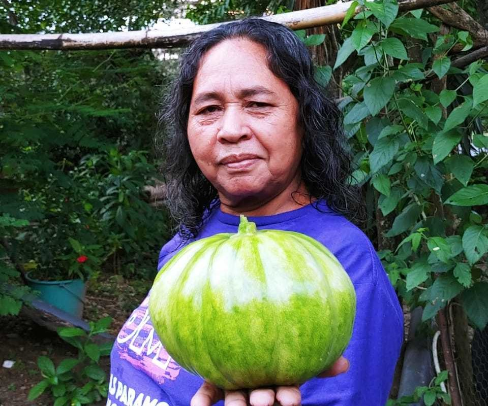 Ana María holding produce from the La Concerta farm