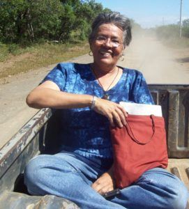 Gilda Larios traveling to visit ESPERA sites in the back of a pickup truck.