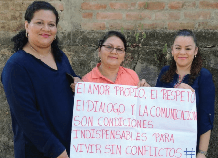 """Dora Alicia, center, is participating in ESPERA's online course. She is pictured with her colleagues Rubidia (left) and Jacqueline (right) showing their hashtag message assignment, which reads: """"Self love, respect, dialogue, and communication are indispensable conditions for living without conflicts."""""""