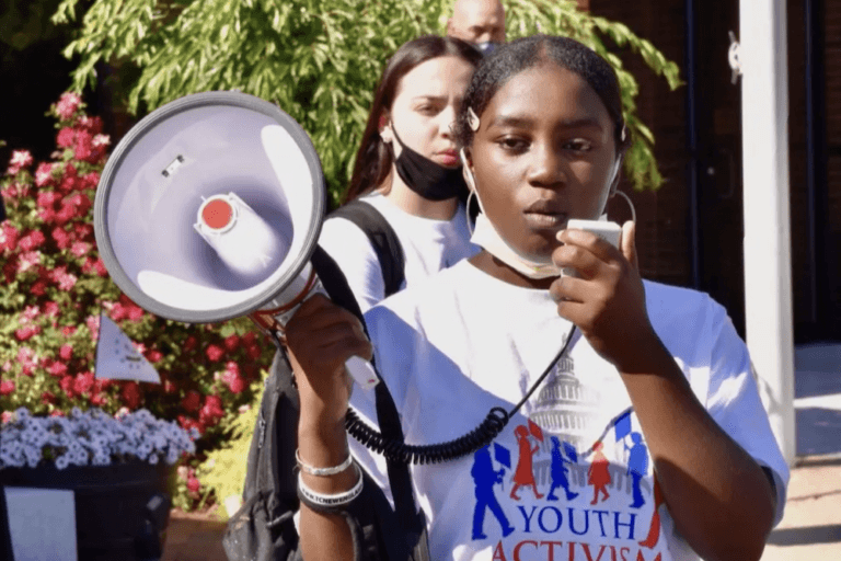 Young woman using megaphone at protest with Mary's Pence Grantee Youth Activism Project