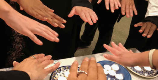 Multicolored hands extending blessing over votive candles.